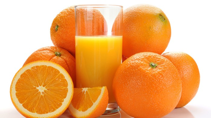 Extreme close-up image of an orange and orange juice on white background